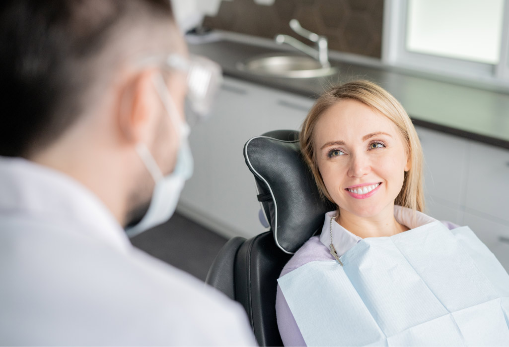 Blonde woman smiles while sitting in the dental chair before root canal therapy to save your infected tooth