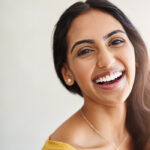 Brunette woman in a yellow shirt smiles after receiving professional teeth whitening in San Antonio, TX