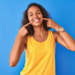 Woman with superb oral health and overall health in a yellow tanktop smiles and points to her teeth against a blue wall