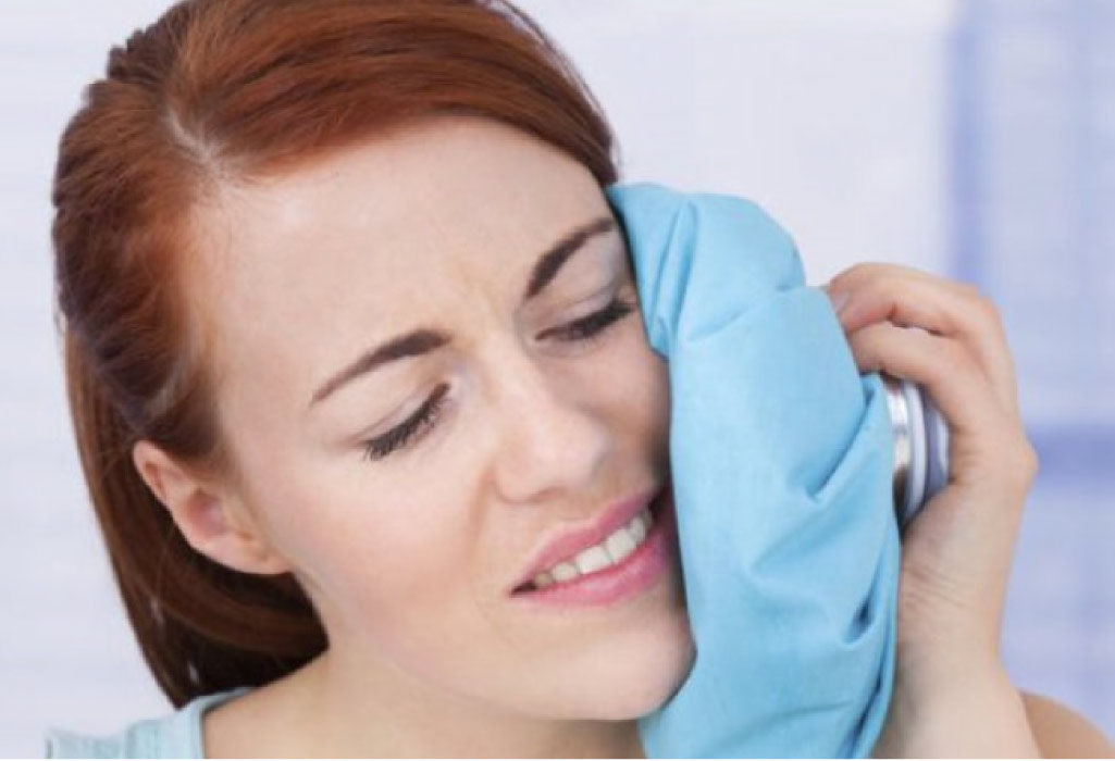 woman holds an ice pack to her cheek after oral surgery