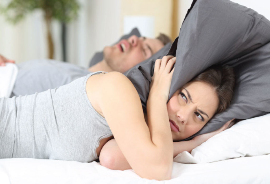 woman covers her head with a pillow to block out her partners sleep apnea snoring