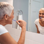 woman looks in the mirror to brush her teeth to maintain good gum health