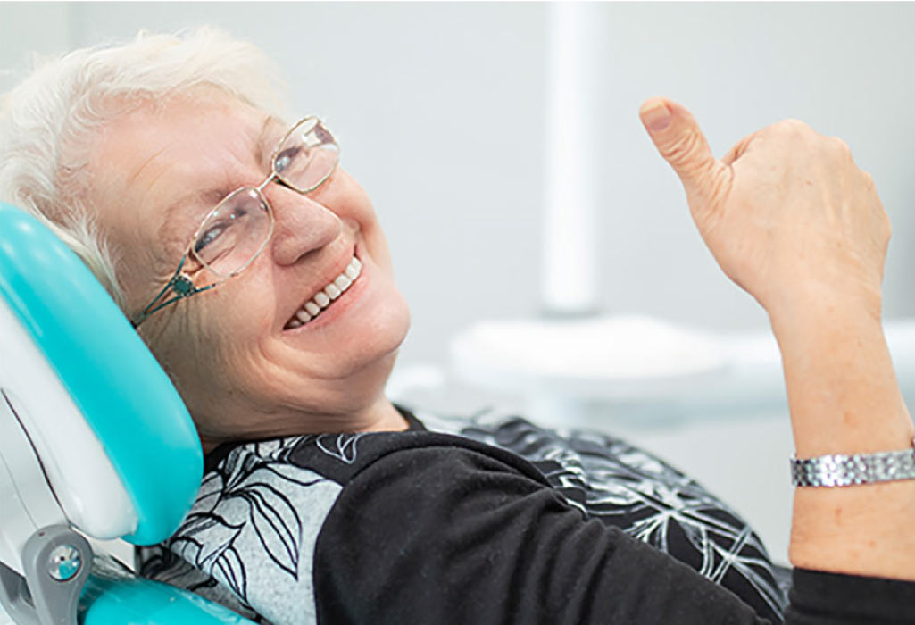 senior woman in the dental chair gives a thumbs up for a good local dentist