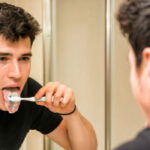young man brushes his tongue to prevent bad breath
