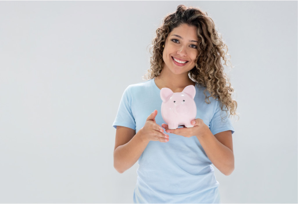 young woman holds a piggybank and smiles after learning about affordable dental plans