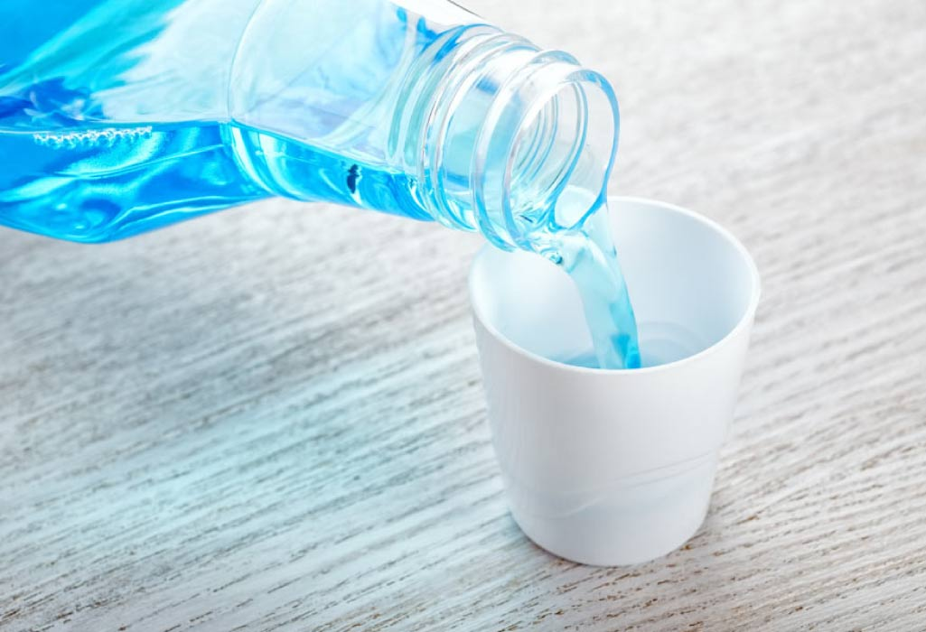 mouthwash being poured into a small cup to fight bad breath