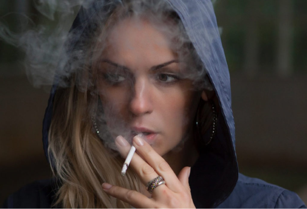 woman wearing a hoodie smokes a cigarette