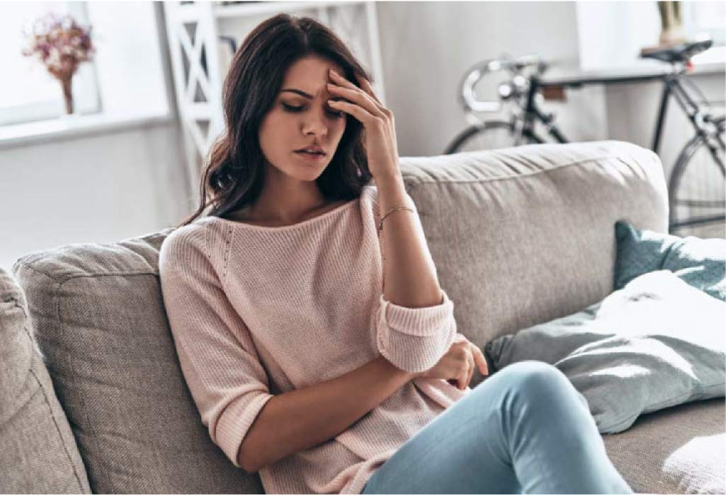 young woman sitting on the couch holding her head in pain from a migraine headache