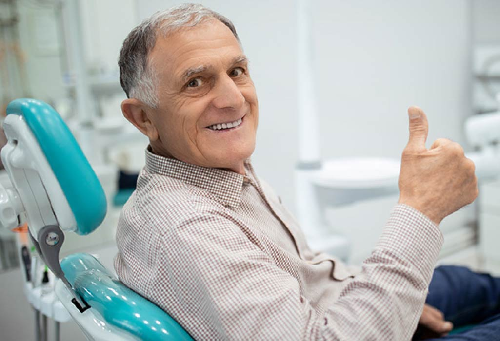 senior man sitting in the dentist chair gives a thumbs up after learning about the connection between diabetes and oral health