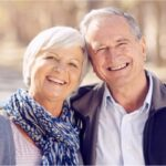 senior couple hug and smile showing off their white teeth